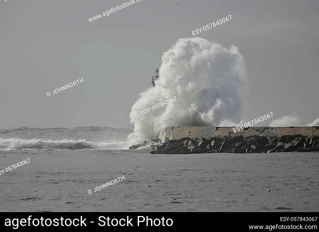 Big wave splash. Ave river mouth pier and beacon, Vila do Conde, Portugal