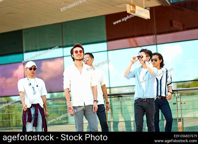 a group of five young asian adults hanging out together walking on street