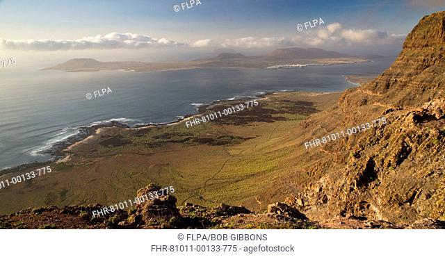View of high volcanic cliffs looking across strait to Isla Graciosa offshore, El Risco, Lanzarote, Canary Islands, March