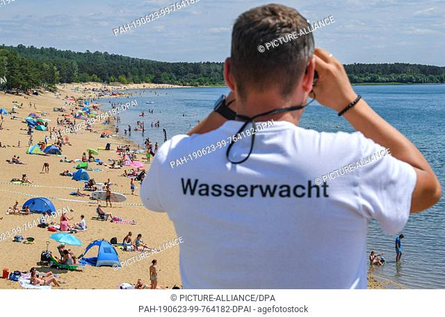 23 June 2019, Brandenburg, Frankfurt (Oder): A lifeguard from the German Red Cross (DRK) observes the bathers in the water of Lake Helene