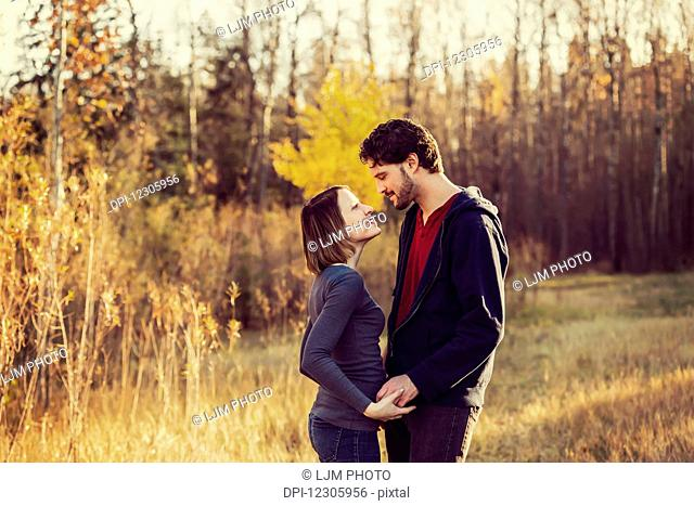A young couple looking into each other's eyes and kissing in a park in autumn; Edmonton, Alberta, Canada