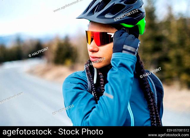 Female mountain biker with sunglasses standing on road outdoors in winter