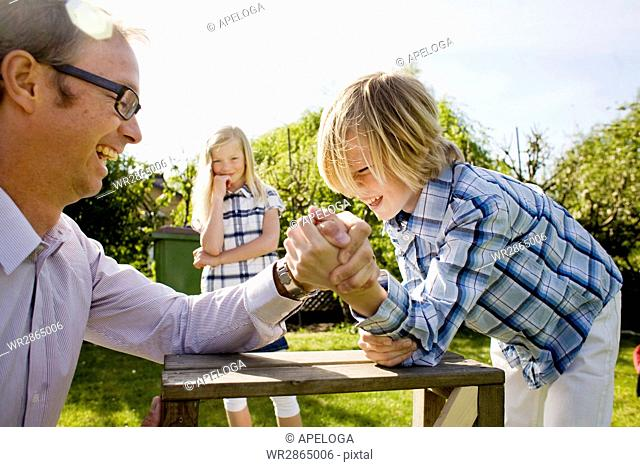 Girl looking at cheerful father arm wrestling with brother at back yard