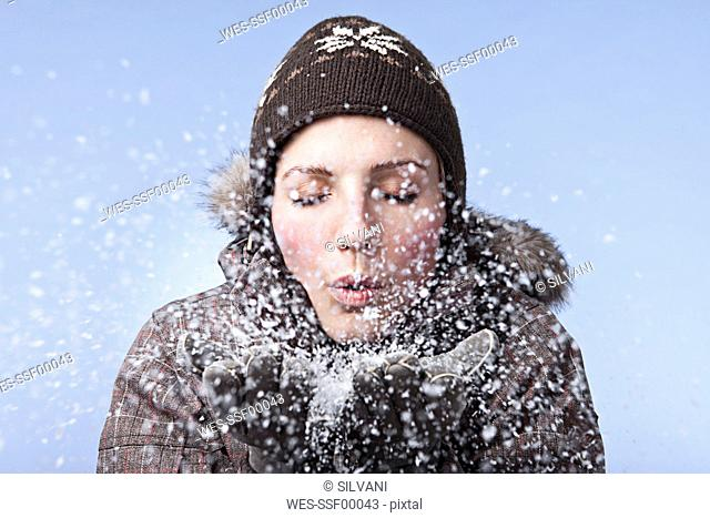 Young woman blowing snow, close-up