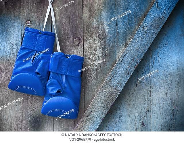 Blue boxing gloves hang on a nail on a wooden shabby wall, empty space on the right