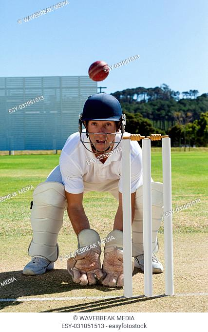 Wicketkeeper looking at ball crouching behind stumps on field