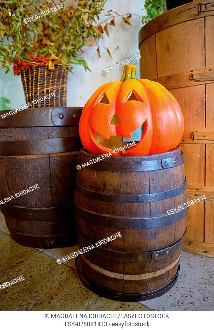 Halloween pumpkin head jack lantern on wooden barrel