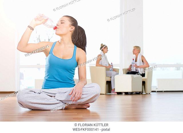 Germany, Brandenburg, Woman drinking water at gym