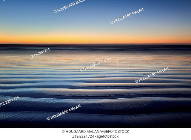 Landscape photo of a rippled beach in pastel nightfall colours. Jacobsbaai, West Coast, South Africa