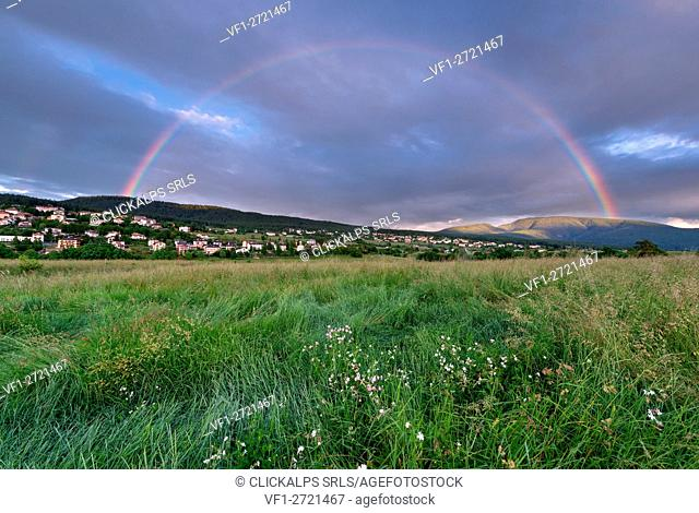 Italy, Trentino Alto Adige, Rainbow at sunset over the prairies of Non valley