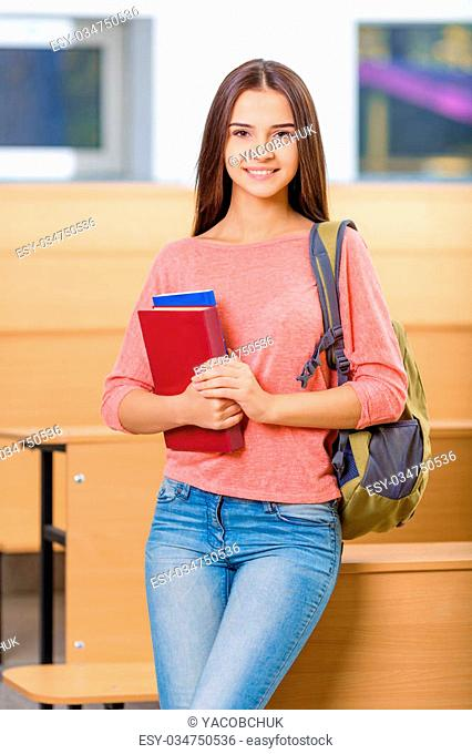 Student life. Appealing young girl is standing in the classroom while holding her textbooks