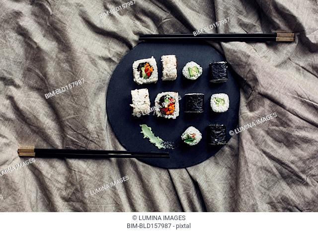Close up of sushi platter with chopsticks in bed