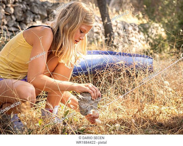 Croatia, Dalmatia, Blonde girl pitching a tent