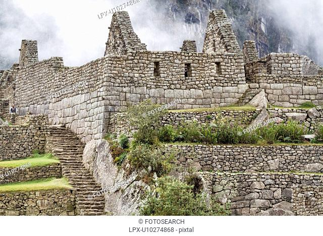 Machu Picchu Inca ruins : detail of agricultural sector terraces and buildings with steep mountain wall beyond in mist, Machu Picchu, Sacred Valley, Peru