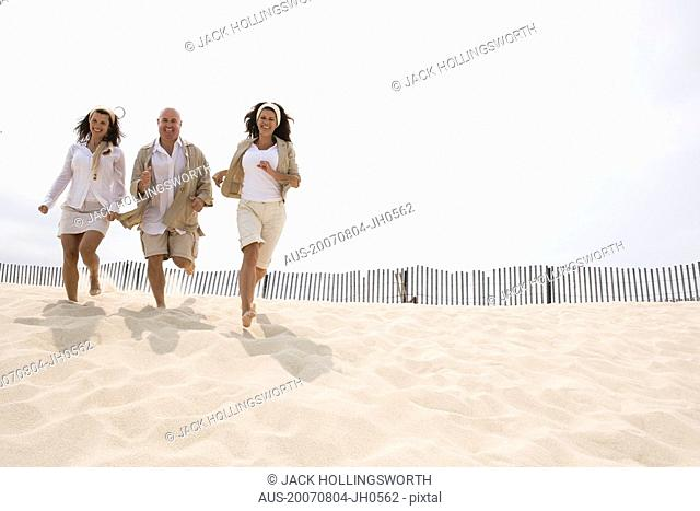 Two mature women and a mature man running on the beach