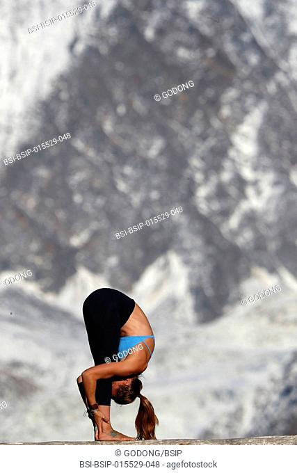 French Alps. Mont-Blanc massif. Woman doing yoga meditation on mountain. Standing forward fold pose. Saint-Gervais. France
