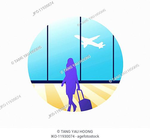 Woman with wheeled suitcase in airport