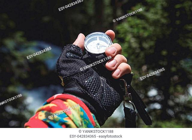 A gloved hand holds a magnetic compass against the background of a coniferous forest and mountain river. The concept of outdoor navigation