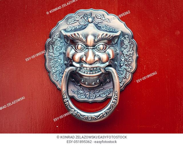 Knocker on a red door of siheyuan courtyard in traditional hutong residential area in Dongcheng district of Beijing, China