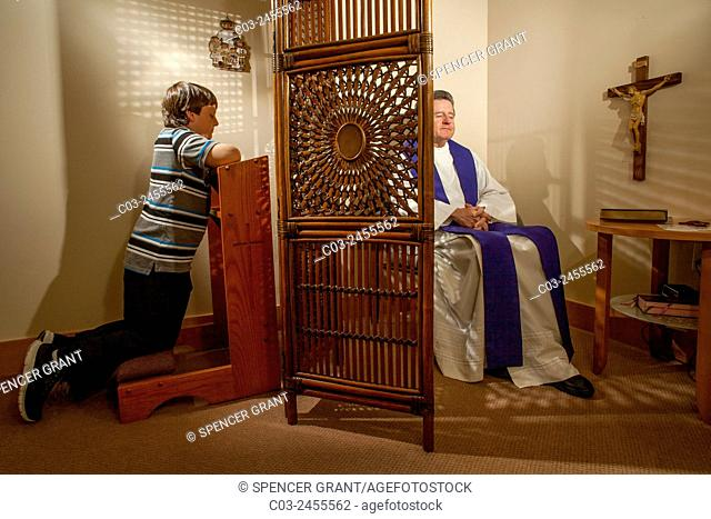 Hidden by a screen, a priest hears confession from a kneeling boy parishioner at a Laguna Niguel, CA, Catholic church. Note vestments. MODEL RELEASE