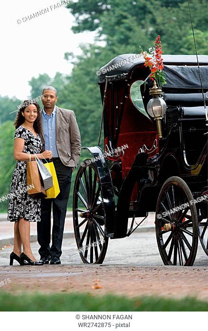 Couple stood next to horse drawn carriage