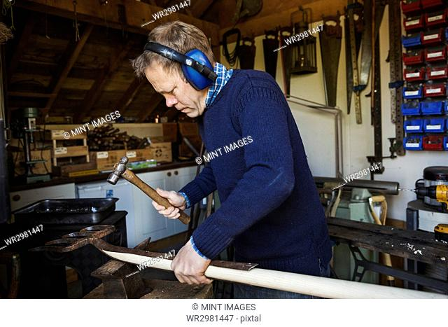 Man standing in a workshop, wearing ear protectors, holding a hammer, working on a piece of wood