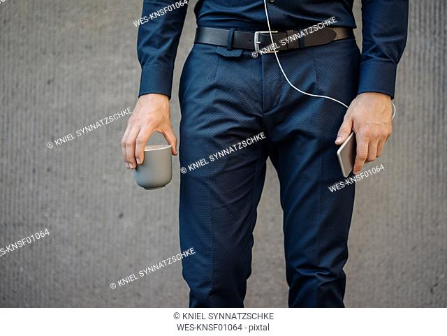 Businessman holding smartphone with connected earphones and cup of coffee