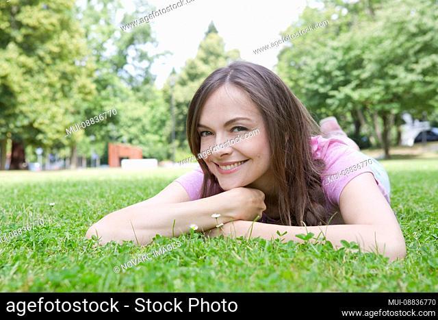 Woman is lying in a meadow