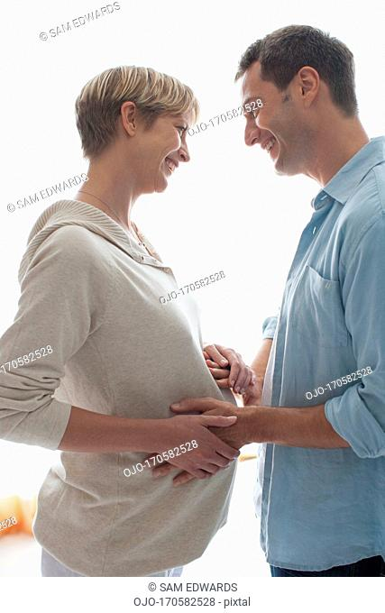 Husband holding pregnant wife's stomach