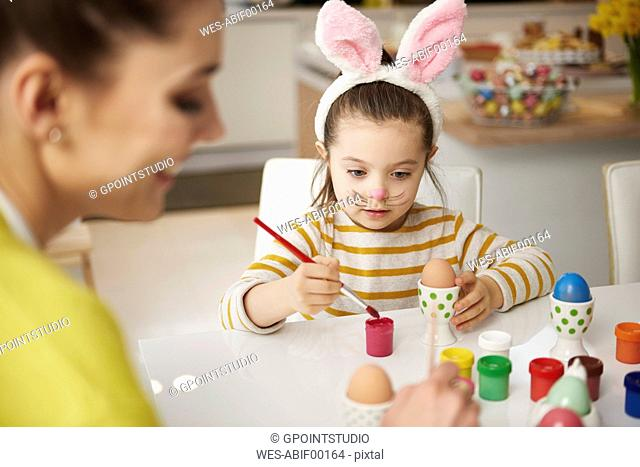 Mother and daughter with bunny ears sitting at table painting Easter eggs