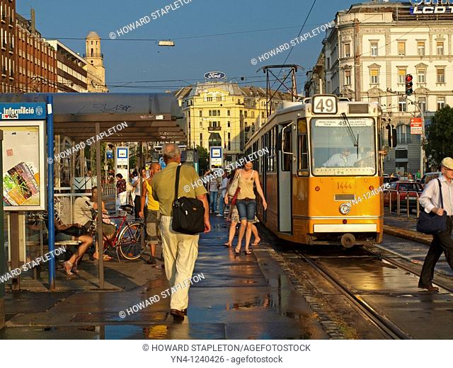 People exit and board a tram at Deak Ter, or Deak Square, in Budapest, Hungary following an afternoon rain shower