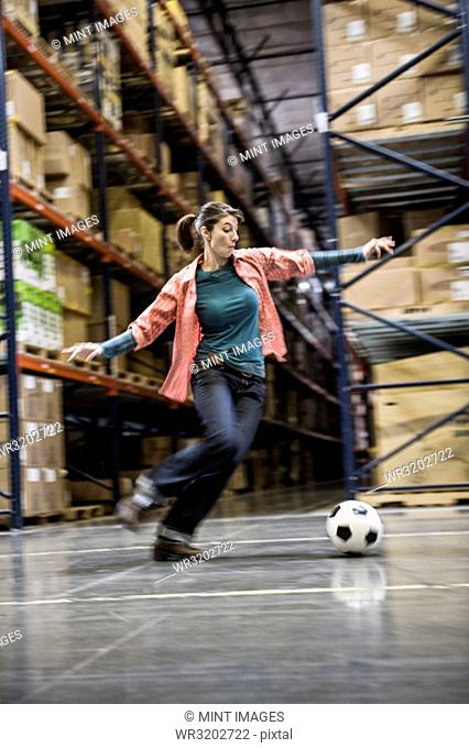 A Caucasian female about to kick a soccer ball during a work break in a distribution warehouse