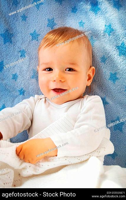 One year old baby lying on blue towel with stars