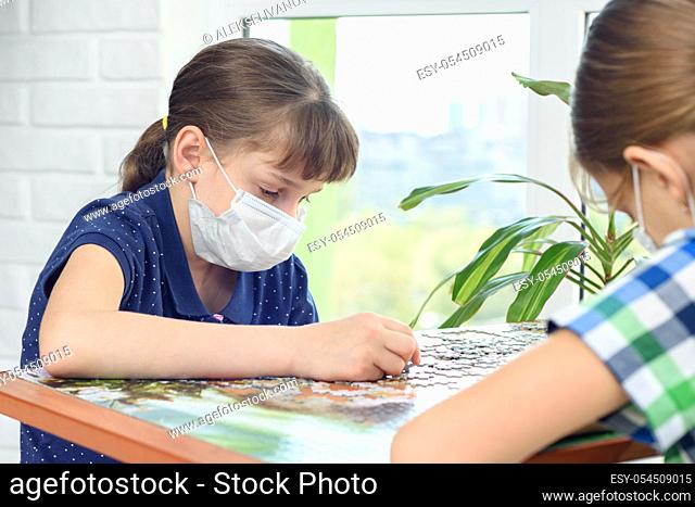 Children at home in protective masks play board puzzles