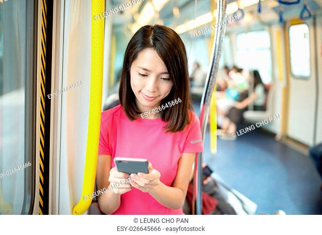 Woman sending sms on cellphone in train compartment