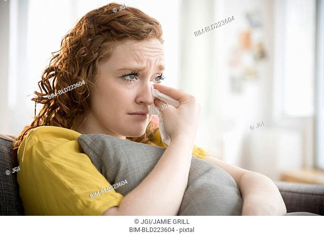 Crying Caucasian woman clutching pillow wiping tears