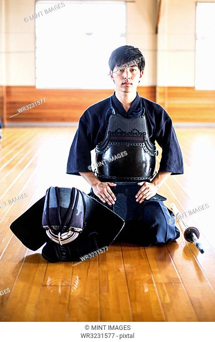 Male Japanese Kendo fighter kneeling on wooden floor, looking at camera