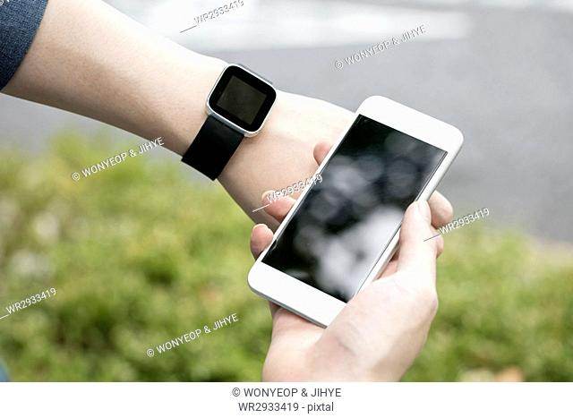 Hands with smartphone and smartwatch