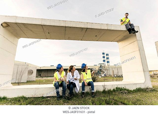 Factory workers having a break, sitting on cnctrete components, man sitting on corner