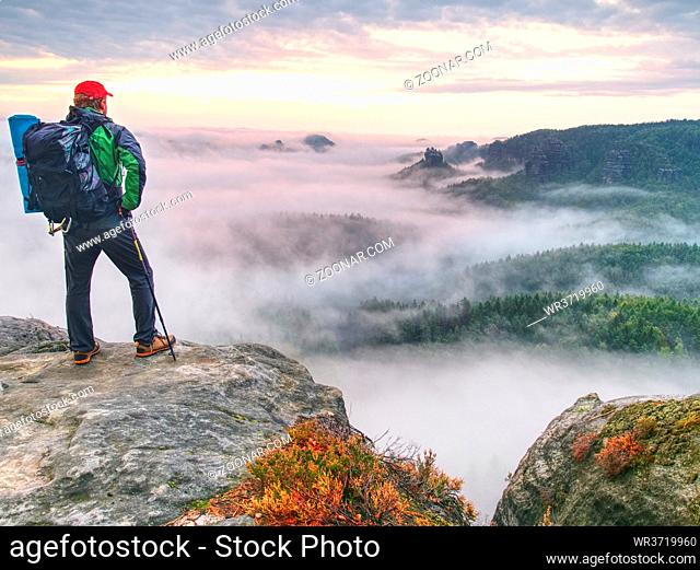 Man stopped for moment walking in foggy rocks. View over thick mist valley to sun hidden at horizon in cold clouds