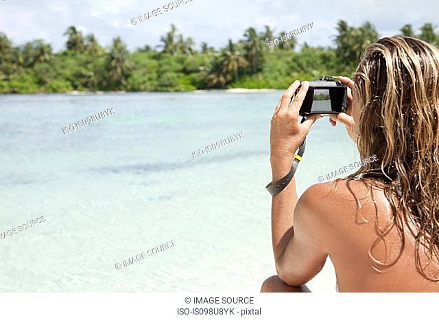 Woman taking picture, Medahutthaa Island, North Huvadhu Atoll, Maldives