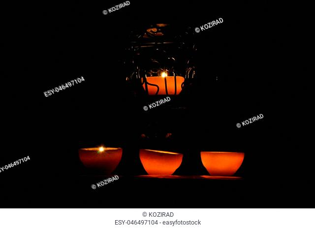 Lamp, candle shining in the darkness. Challis flame. Artistic composition. Lighting