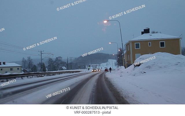 Driving through a Swedish town in winter: a lonely pedestrian walks along the road. Kramfors, Västernorrlands Län, Sweden