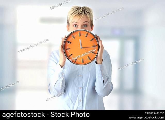 Woman holding big alarm clock