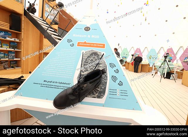 12 May 2020, Thuringia, Gera: A hiking boot hangs on an information board on the subject of the ecological footprint in the Climate Pavilion