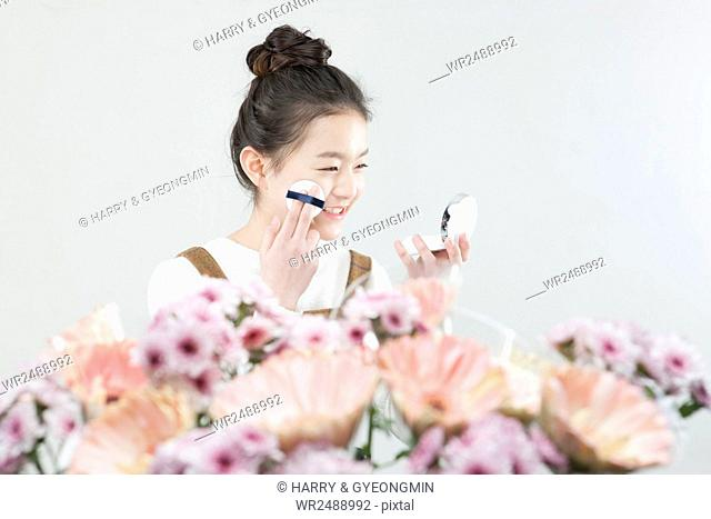 Side view portrait of smiling school girl putting on make-up with flowers
