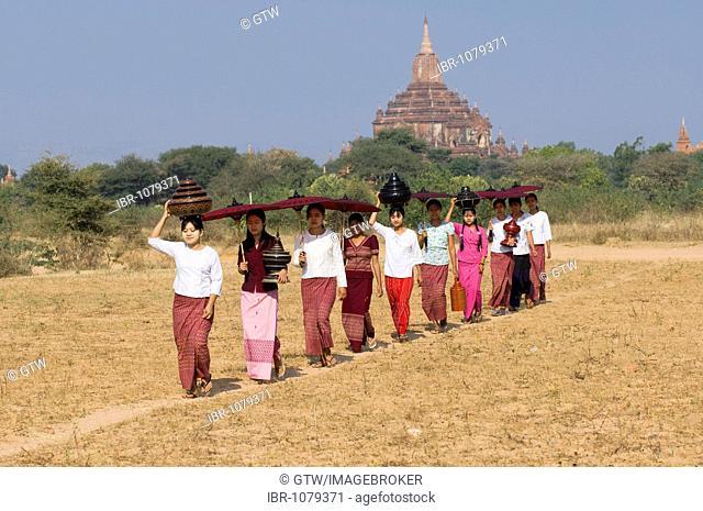 Young Burmese women with a parasol crossing a field near the Sulamani Pagoda, Bagan, Myanmar