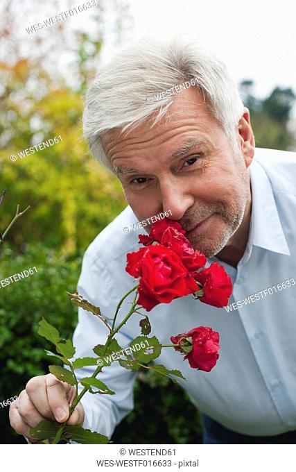 Germany, Kratzeburg, Senior man smelling roses