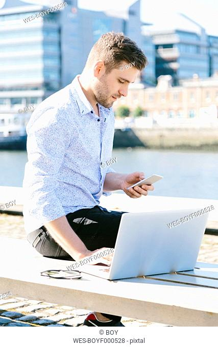 Ireland, Dublin, young businessman sitting on bench using laptop and cell phone