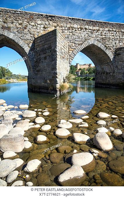 The Romanesque bridge across the River Tormes at El Barco De Avila with the castle in the background,, Avila Province, Spain